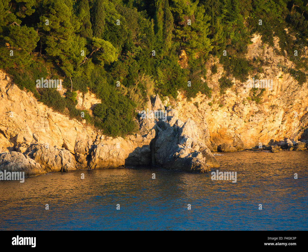 Sunset on the Dalmatian coast of the Adriatic sea makes the cliffs turn golden , here the outskirts of Dubrovnik - Stock Image