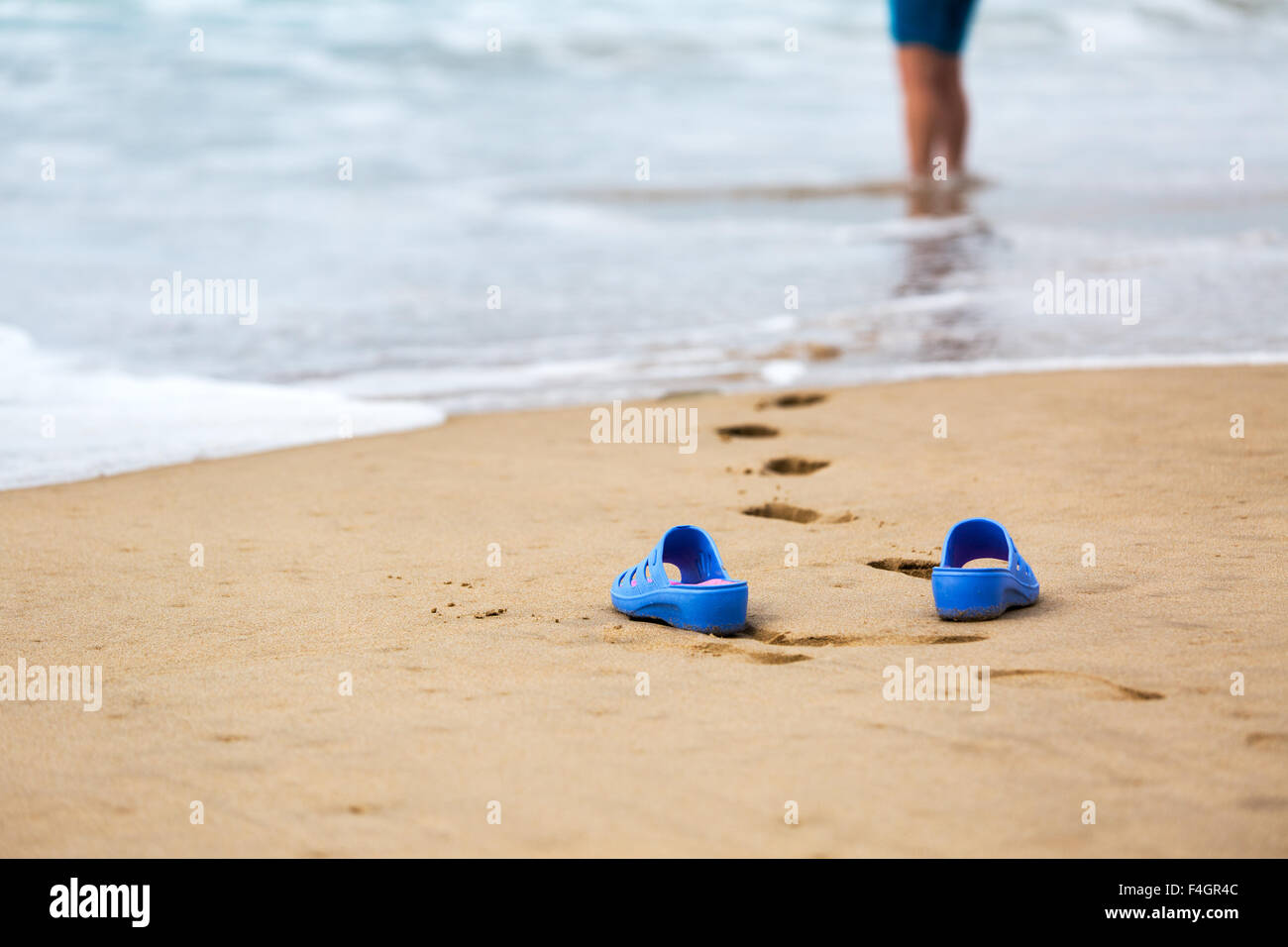 39066da2e3bb8a Beach Slippers in the Foreground and Blurred Silhouette of a Woman in Waves  - Stock Image