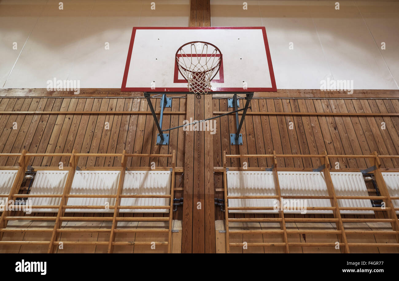 Old basketball hoop in an old gymnasium - Stock Image
