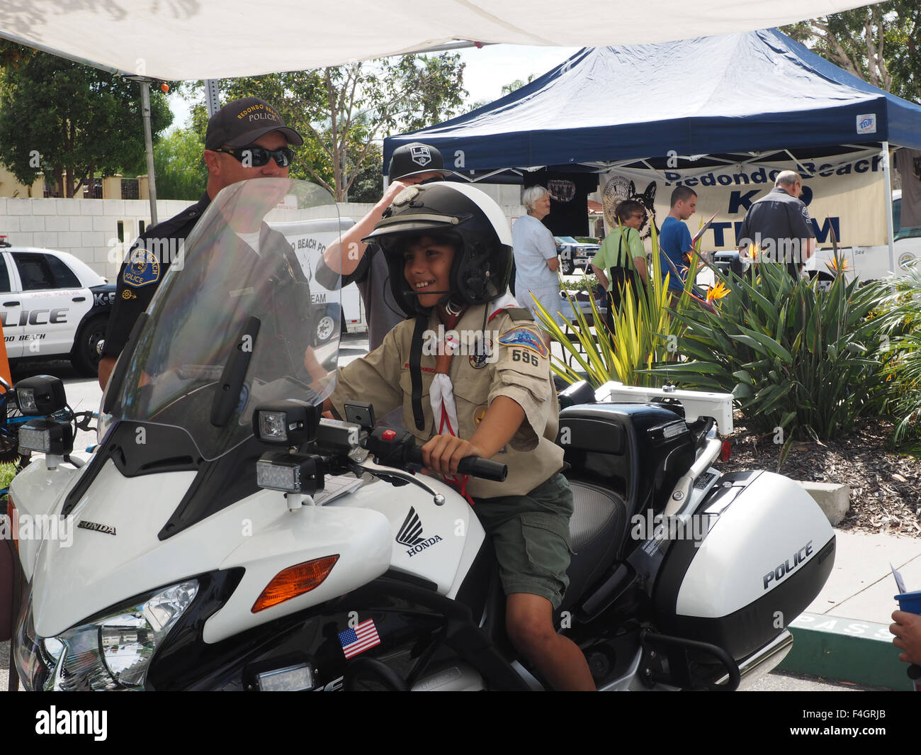 Latino boy scout astride police motorcycle at police fair. Redondo Beach, CA.. - Stock Image