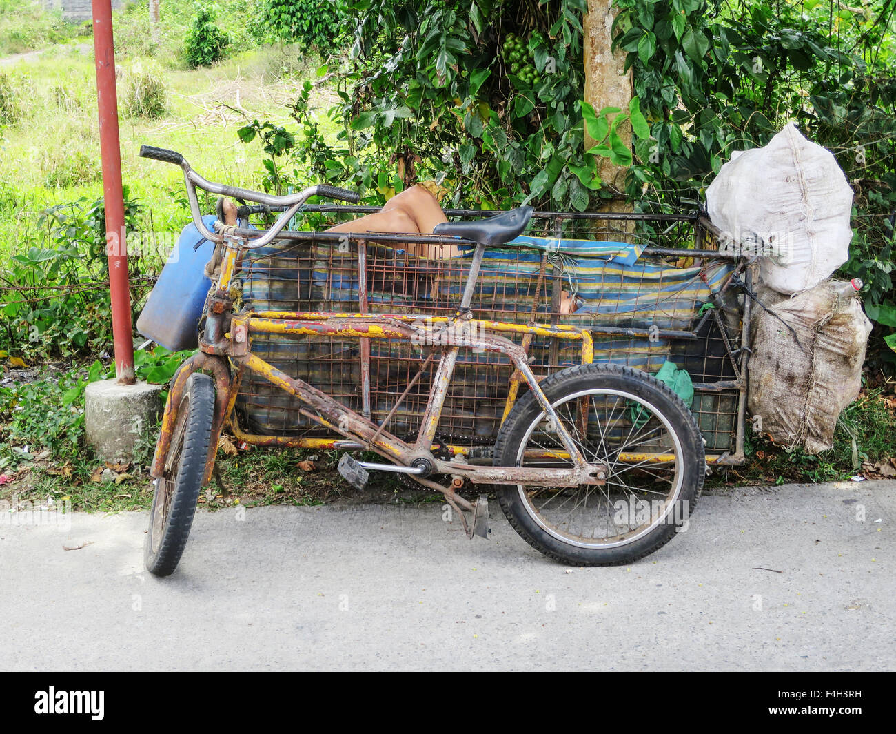 A Filipino man takes an afternoon siesta from his work collecting bottles inside the sidecar of his bicycle. - Stock Image