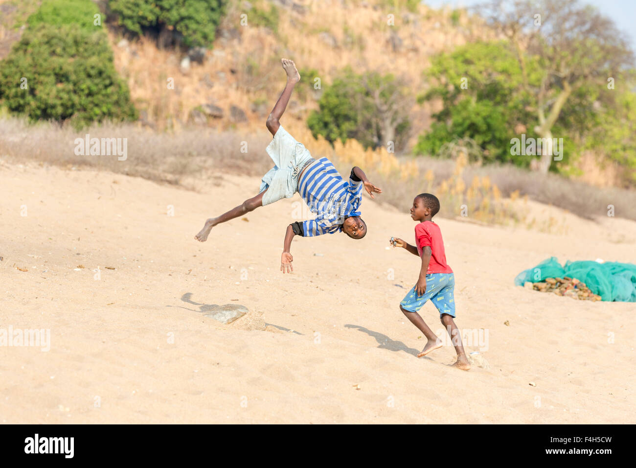 Local children and lifestyle: acrobatic boys playing, jumping, turning somersaults on the beach, Likoma Island, Stock Photo