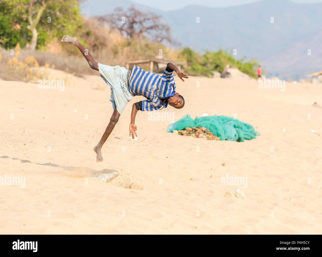 Local acrobatic boy playing, jumping, turning somersaults on the beach, Likoma Island, Lake Malawi, Malawi, south Stock Photo