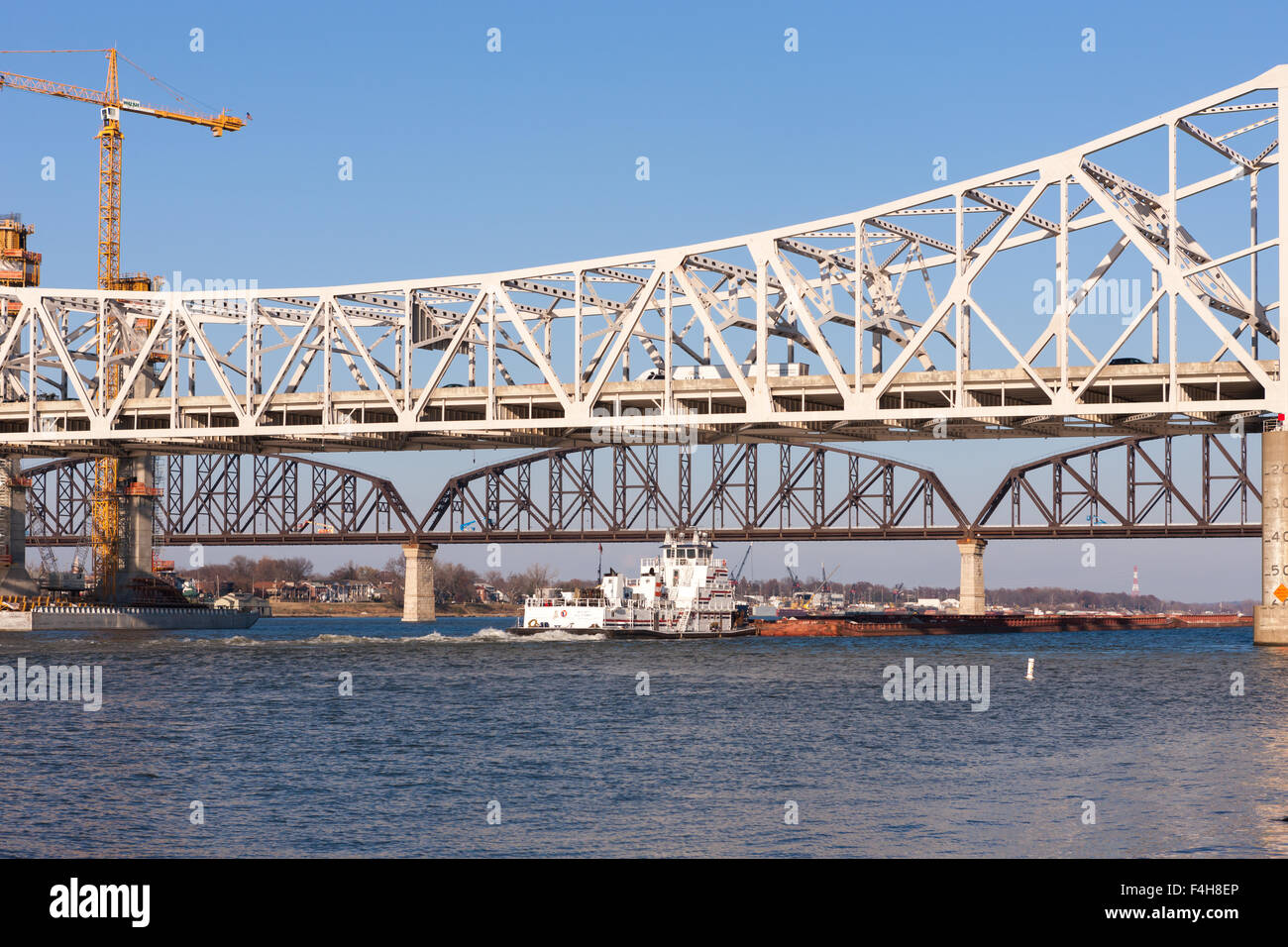 AEP River Operations towboat Captain Bill Stewart pushes a barge load east on the Ohio River in Louisville, Kentucky. - Stock Image