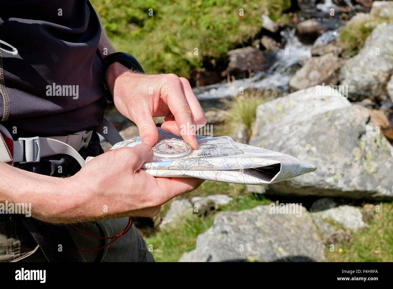 Hiker taking a bearing using a hiking map and compass for navigating a right direction in British mountains seen - Stock Image