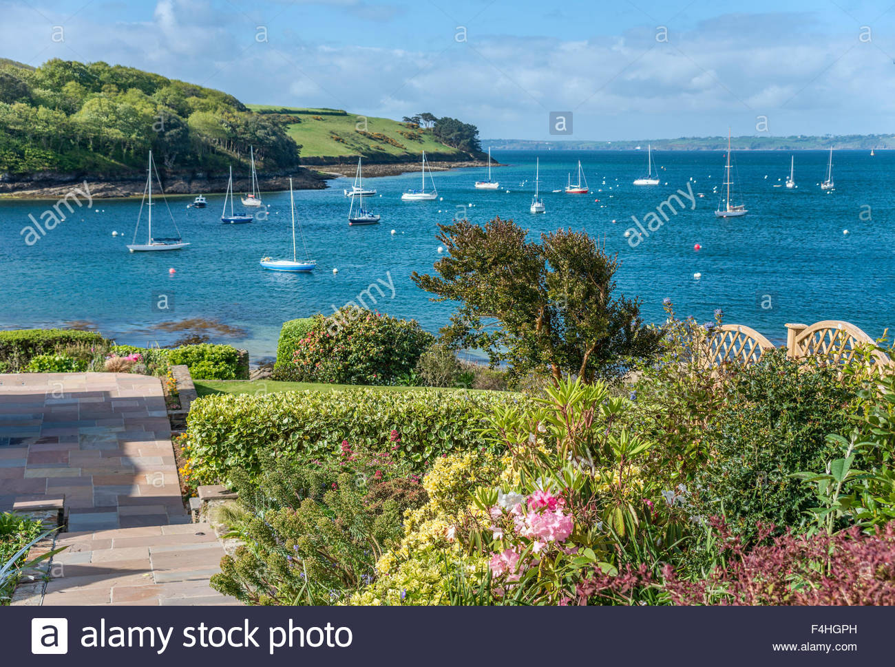 View over a garden at the scenic coastline near the village St.Mawes at the Cornish Coast near Falmouth, Cornwall, - Stock Image