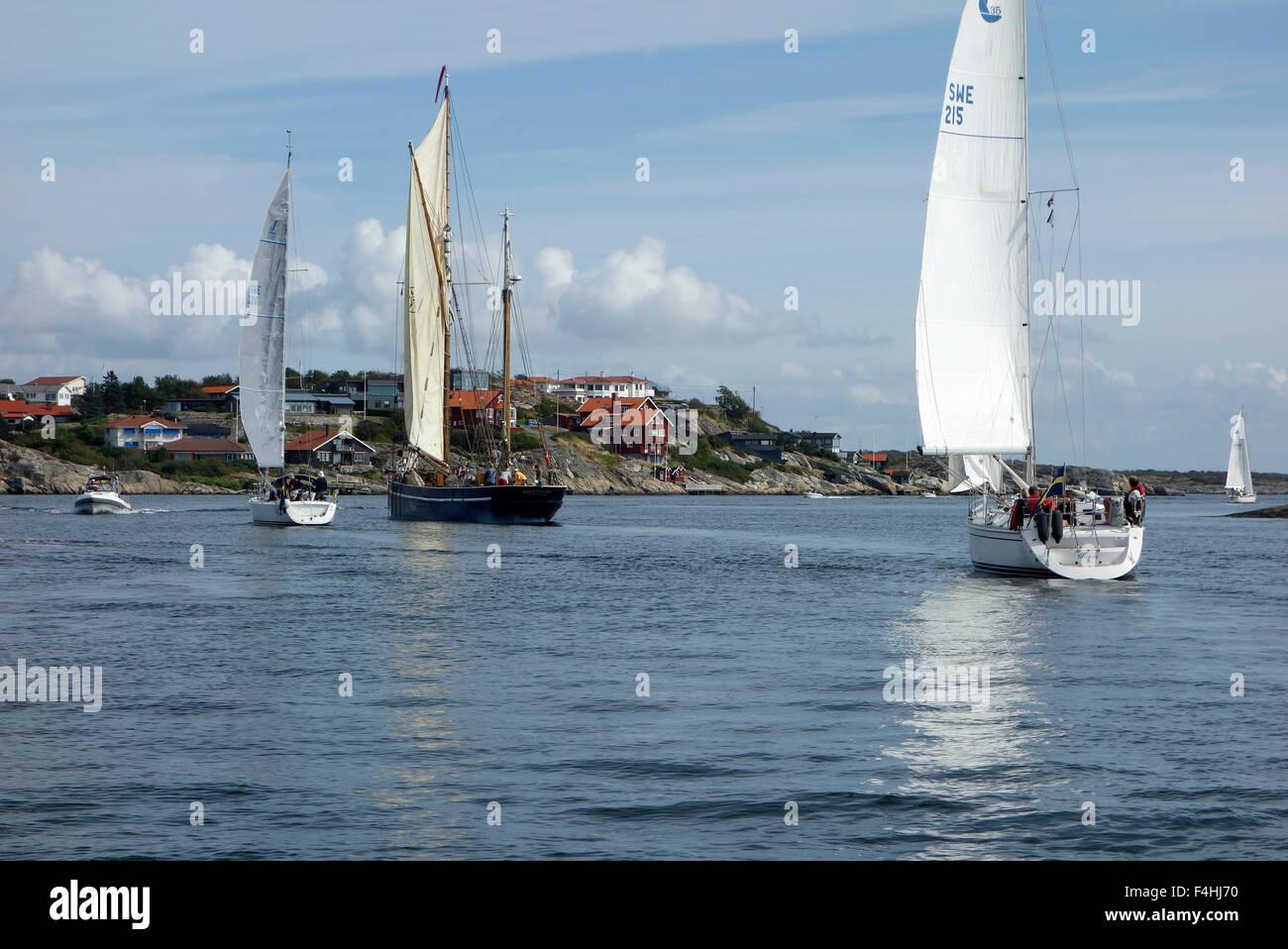 Cruising sailboats  in sound between  Stora Varholmen island and Hjuvik koast on Swedish West coast. Gothenburg, Stock Photo