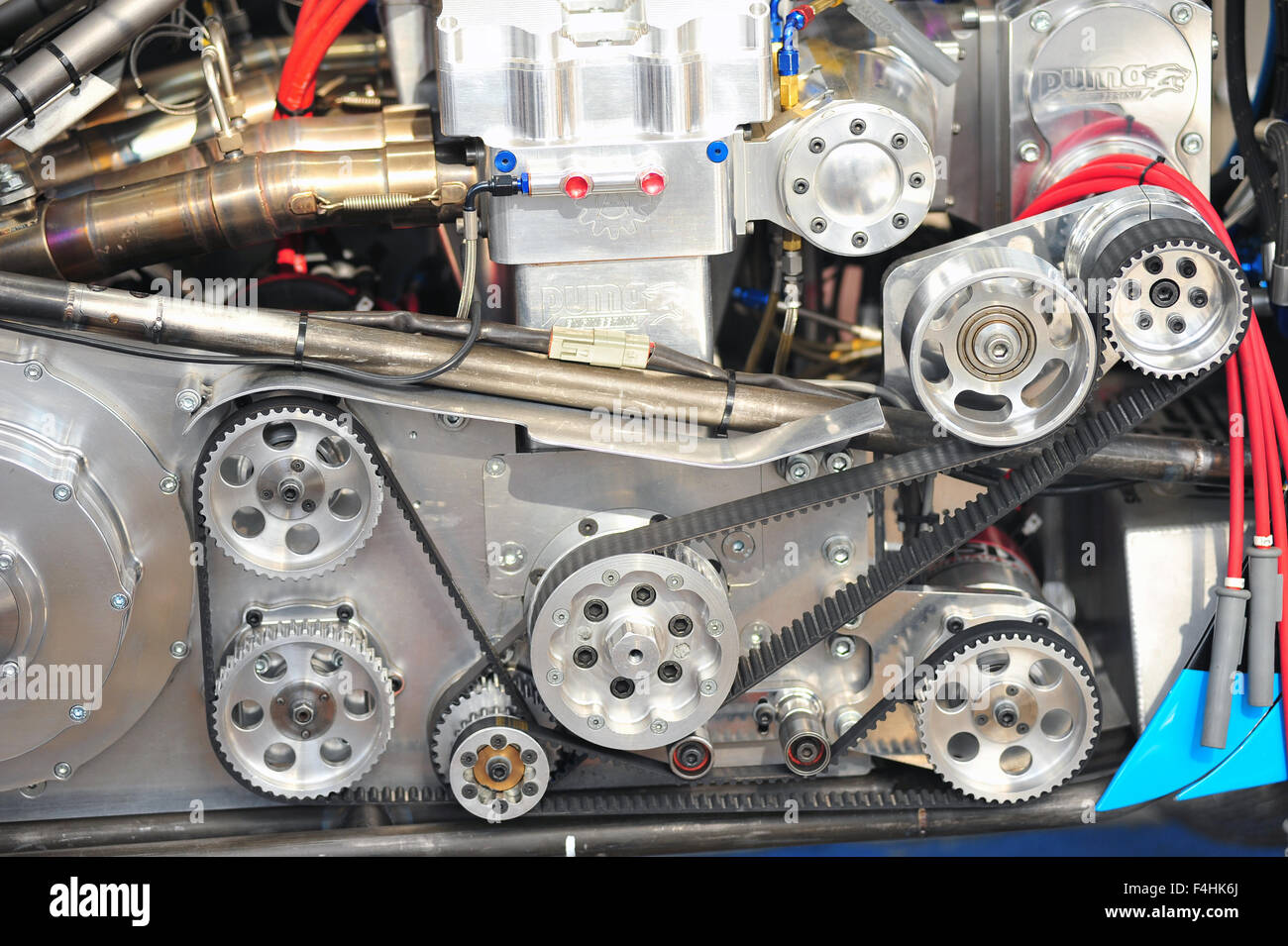 The auxiliary belts and wheels on the side of a racing engine at the Goodwood Festival of Speed. - Stock Image