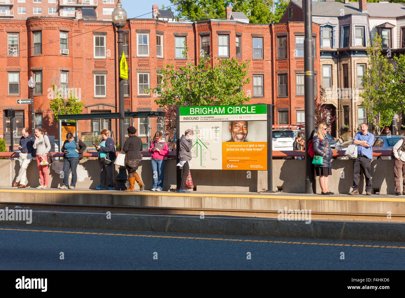 People wait for an inbound train at the Brigham Circle Station on the MBTA Huntington Avenue Line in Boston, Massachusetts. - Stock Image