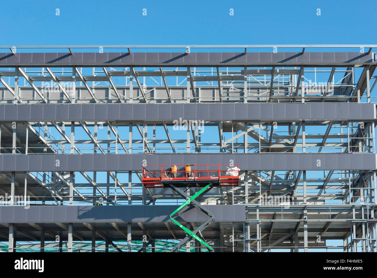 Scissor lift access platform on building site, Poyle, Berkshire, England, United Kingdom - Stock Image