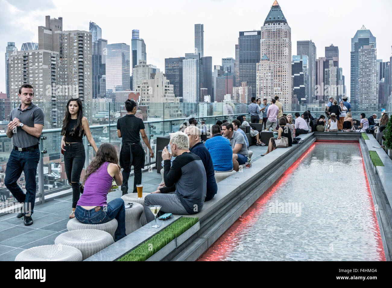 young crowd clusters around reflecting pool on terrace of Ink 48 hotel rooftop bar enjoying drinks socializing & - Stock Image