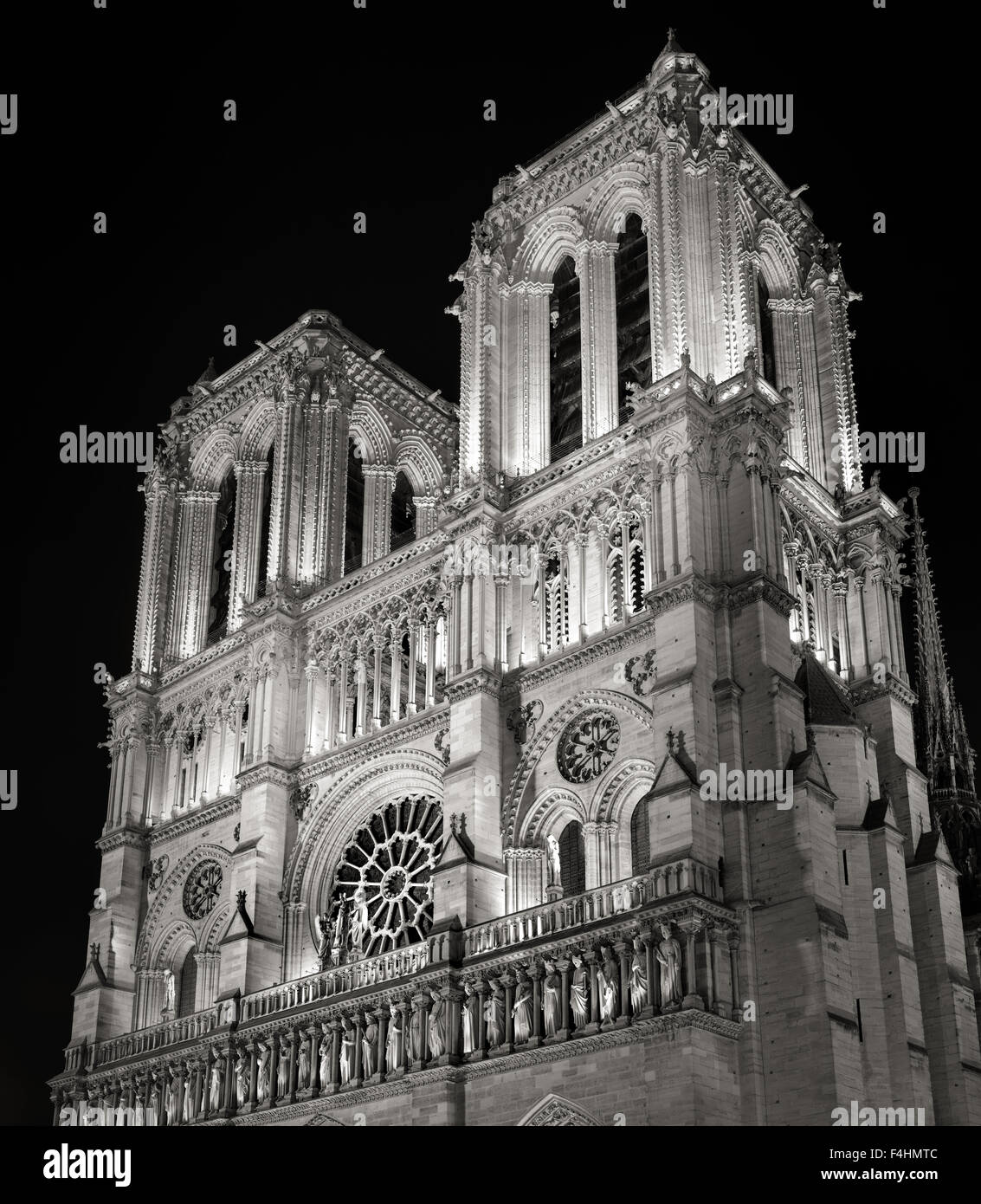 Towers and Facade of Notre Dame de Paris Cathedral illuminated at night, Ile de la Cite, France. French Gothic Architecture - Stock Image