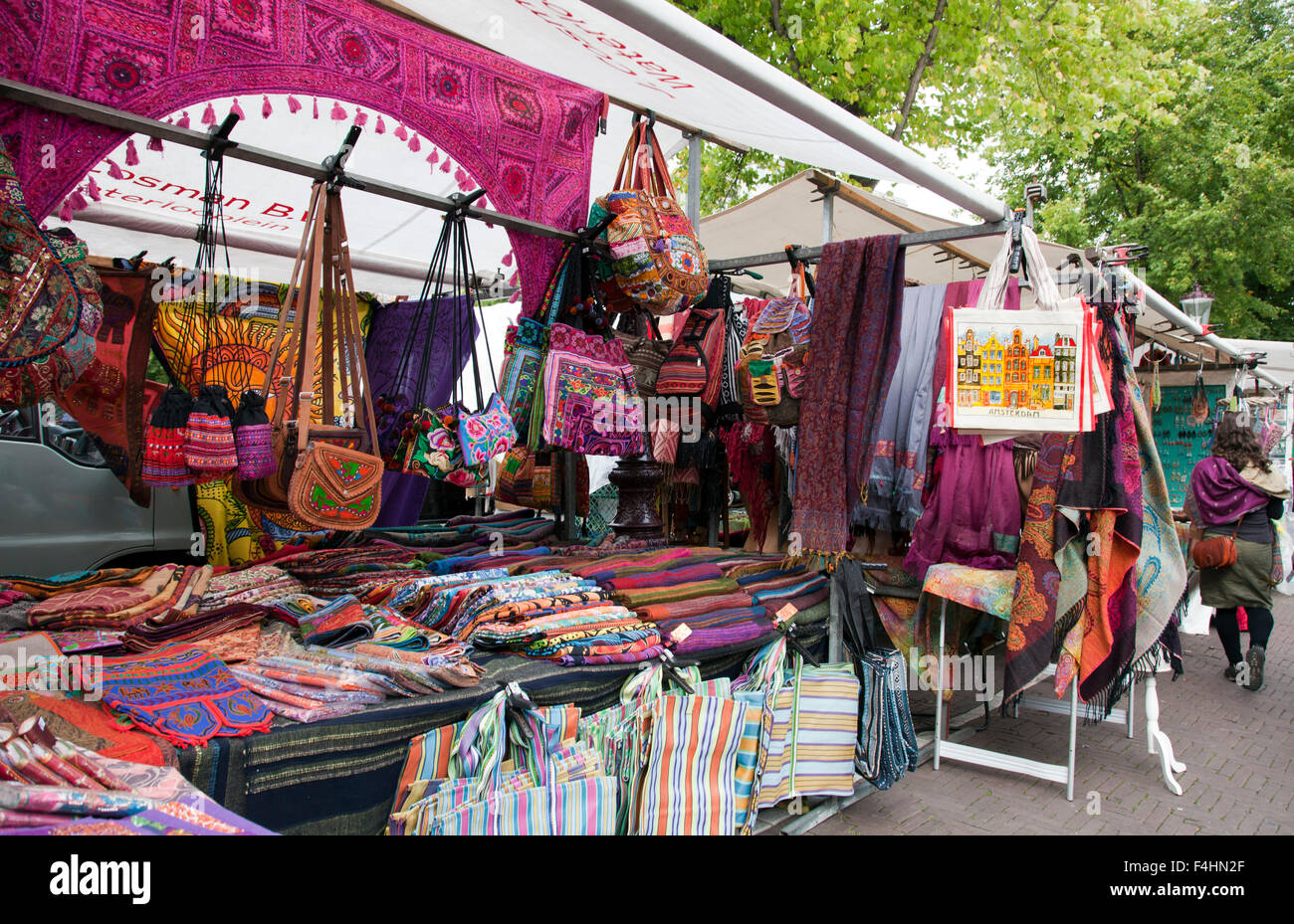 Wildly colorful textiles tempt shoppers at the Waterlooplein flea market in the center of Amsterdam. - Stock Image
