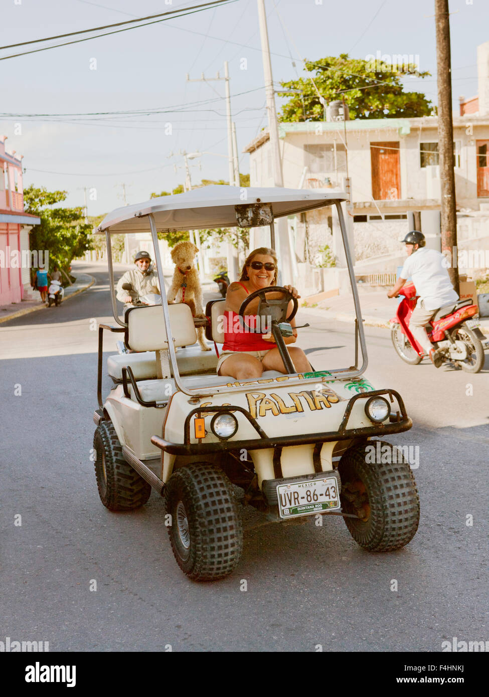 A local ex- pat drives her golf cart through town. IIsla Mujeres, Quintana Roo, Mexico. - Stock Image