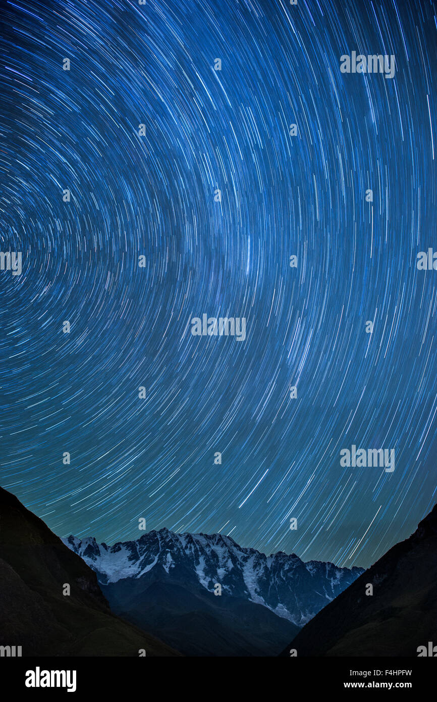 Moonlit view of star trails above Mount Shkhara (5193m), the highest mountain in Georgia. - Stock Image