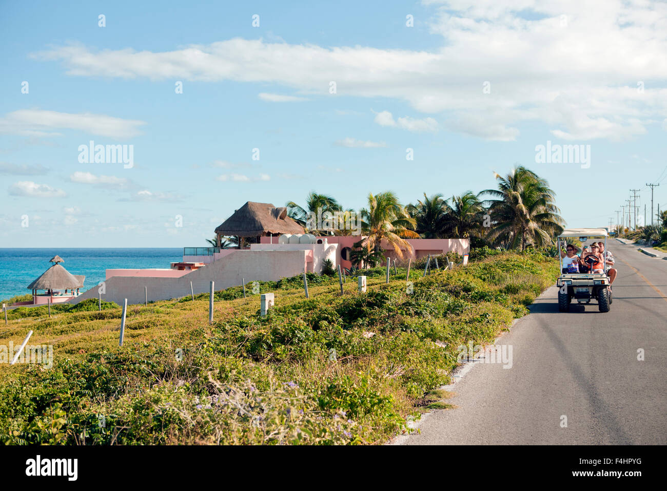 Tourists riding golf carts on Rueda Medina, a main road that runs from Playa Norte to Punta Sur in Isla Mujeres, - Stock Image