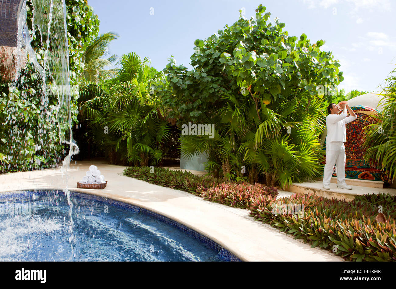 A young Mexican man blows a conch shell to signal the start of the Temazcal treatment at Spa Aqua at Live Aqua Resort - Stock Image