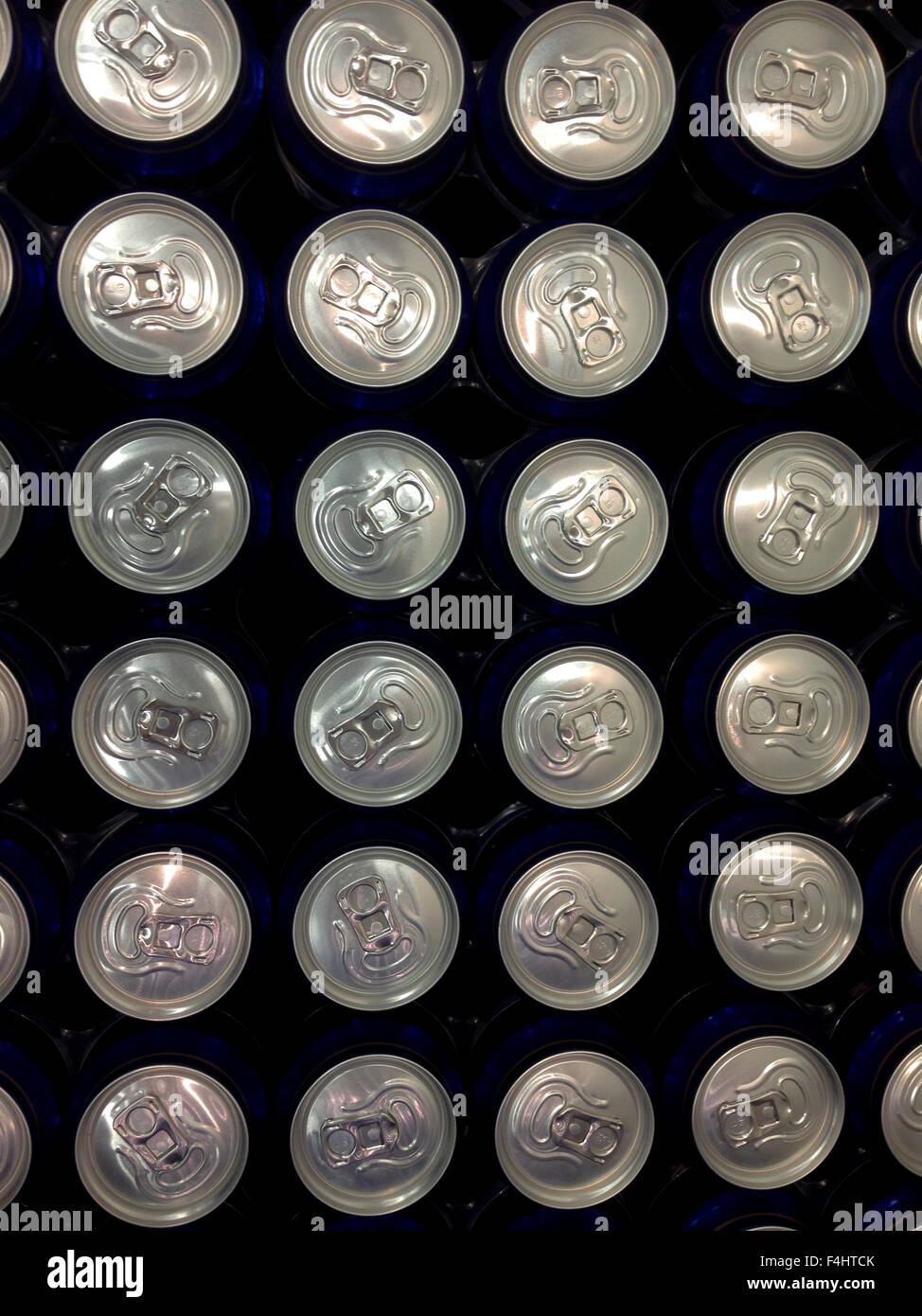 Lines of of blue tins of beer on supermarket - Stock Image