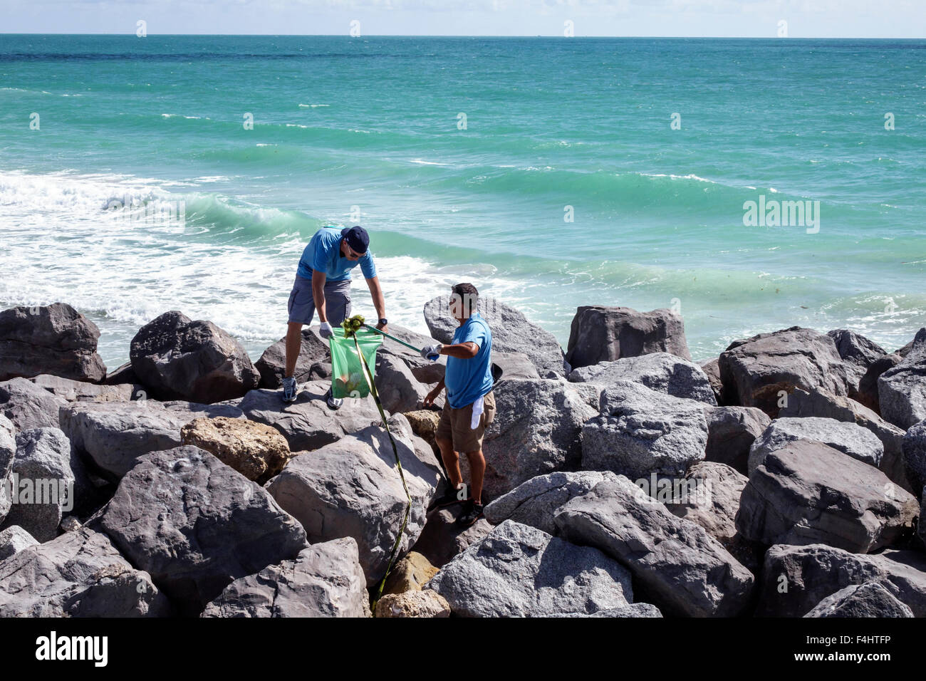 Miami Beach Florida clean-up cleanup clean up volunteer man Hispanic collecting trash litter community service Impact - Stock Image