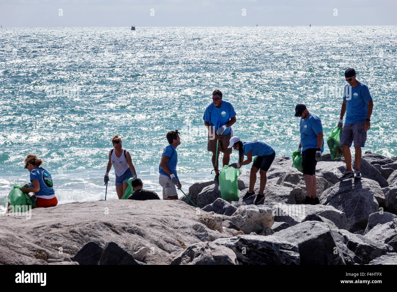 Miami Beach Florida clean-up cleanup clean up volunteer man woman Hispanic collecting trash litter community service - Stock Image