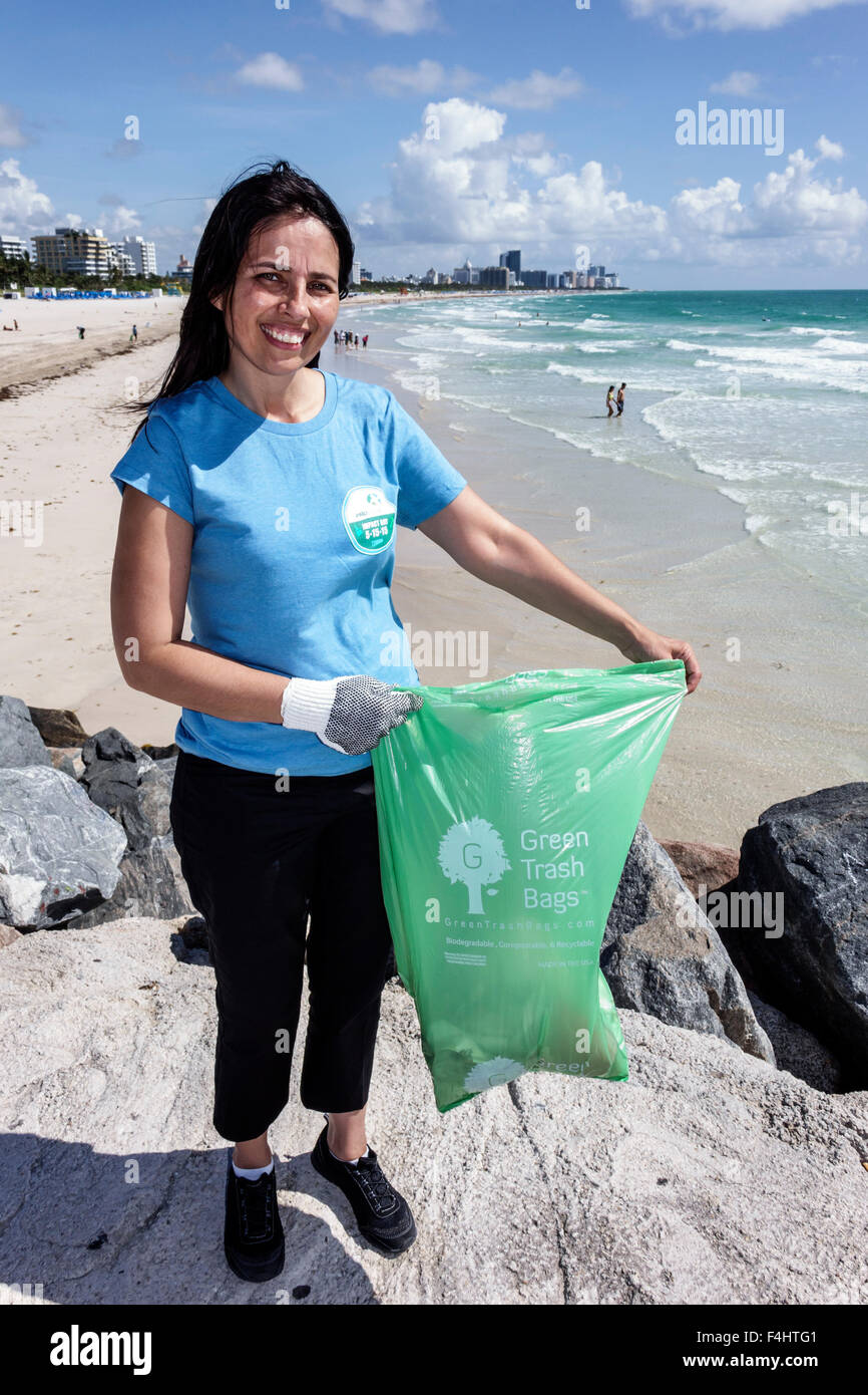 Miami Beach Florida clean-up cleanup clean up volunteer woman Hispanic collecting trash litter community service - Stock Image