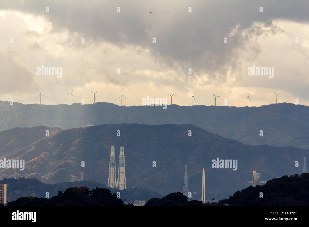 Wakayama, Japan, silhouetted wind turbines on top of distant mountains with various industrial chimneys in foreground. - Stock Image