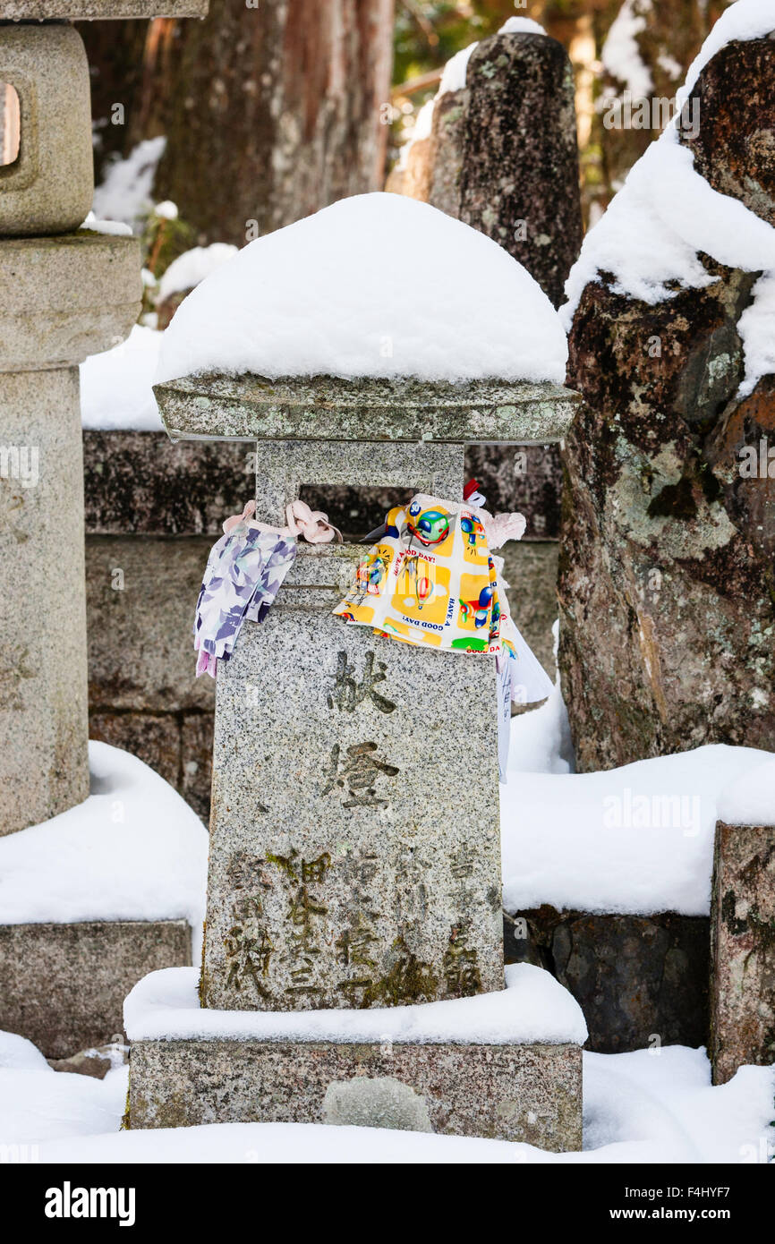 Japan, Koyasan, famous Okunoin cemetery. Snow topped grave memorial stone with bibs left as offerings tied to side. - Stock Image