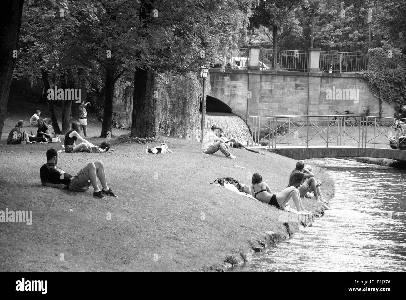 Munich Englischer Park, Germany-July 08: Unidentified people relaxing in the park in front of the river on July - Stock Image