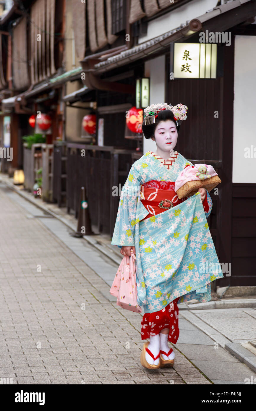 Maiko, apprentice geisha, walks to evening appointment past traditional wooden buildings, Gion, Kyoto, Japan, Asia - Stock Image