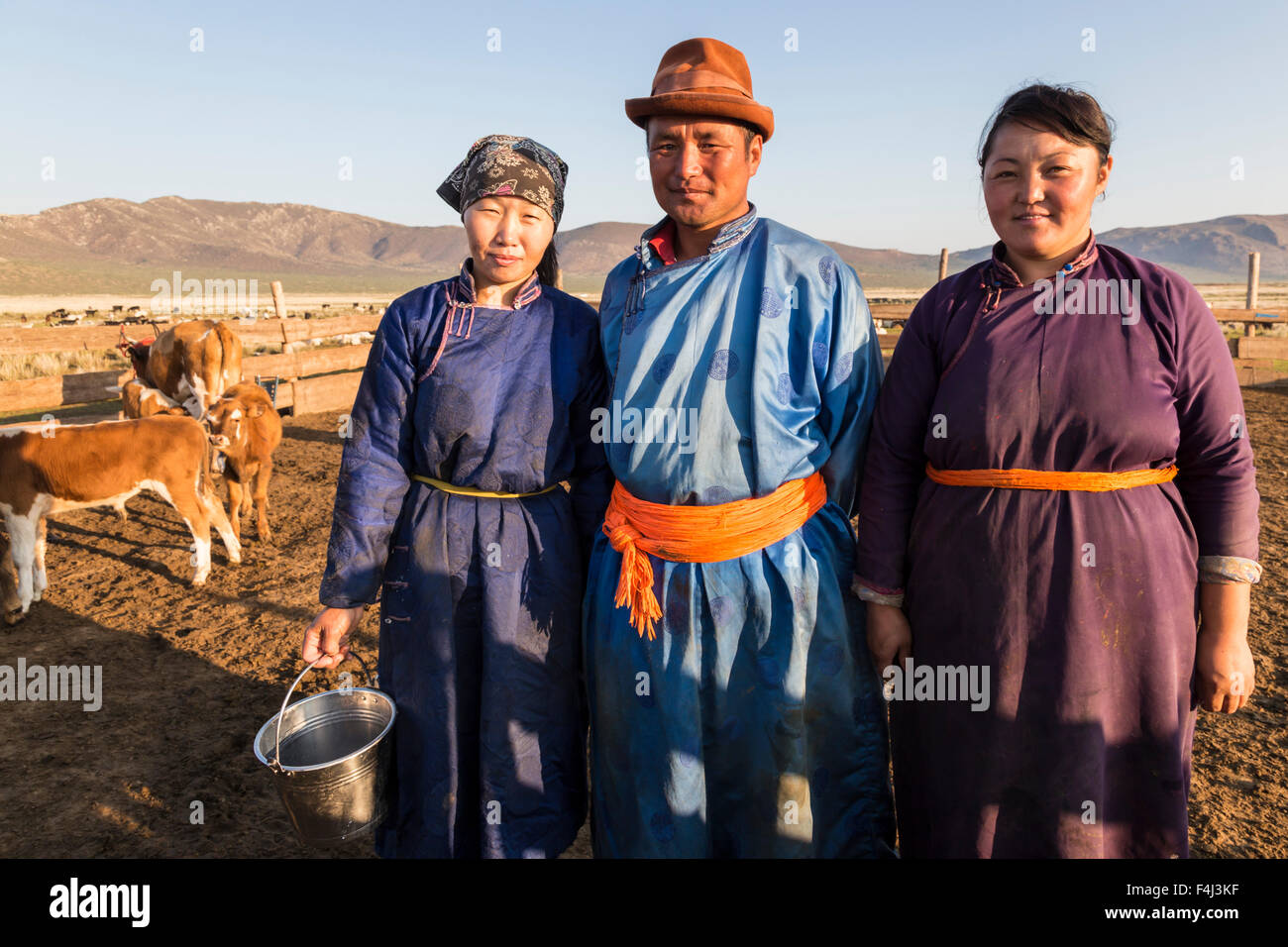 Smiling nomadic people in traditional clothes (deels) in milking pen at daw in summer, Nomad camp, Gurvanbulag, - Stock Image