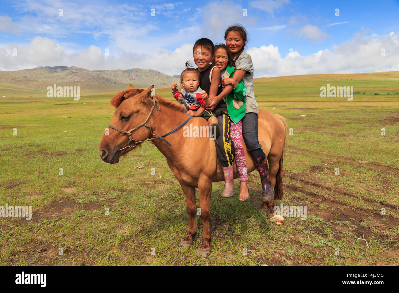 Four nomad siblings on their tame horse at summer nomad camp, Khujirt, Uvurkhangai, Central Mongolia, Central Asia, - Stock Image