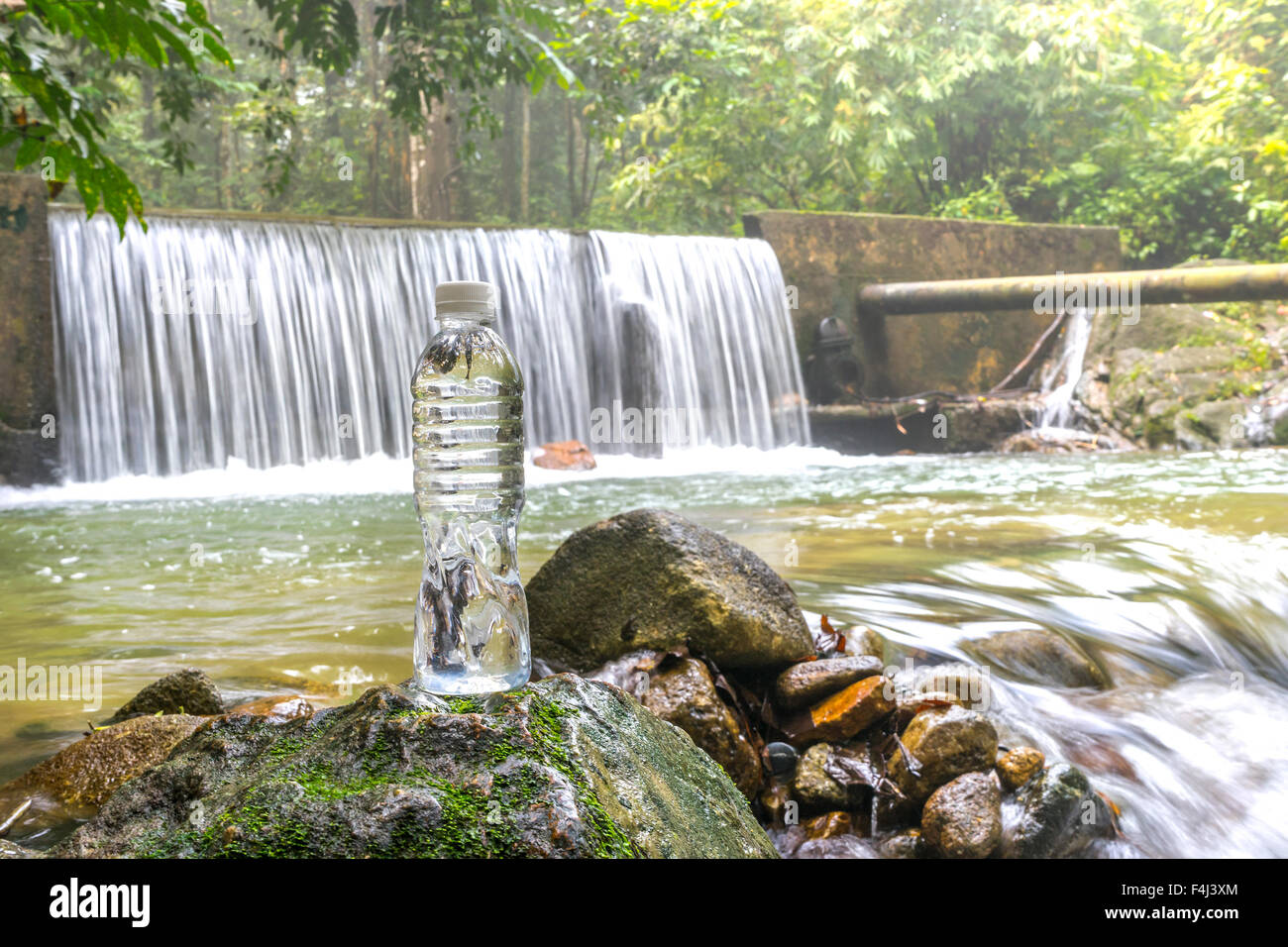 Plastic bottle with waterfall background at tropical forest Stock Photo