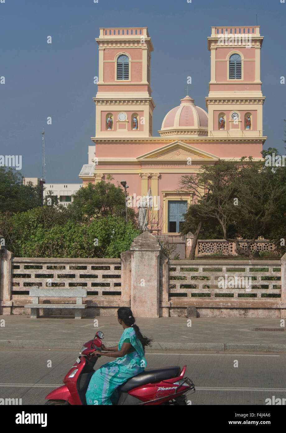 Local woman drives motorbike past traditional French architecture in the union territory of Pondicherry, Tamil Nadu, - Stock Image
