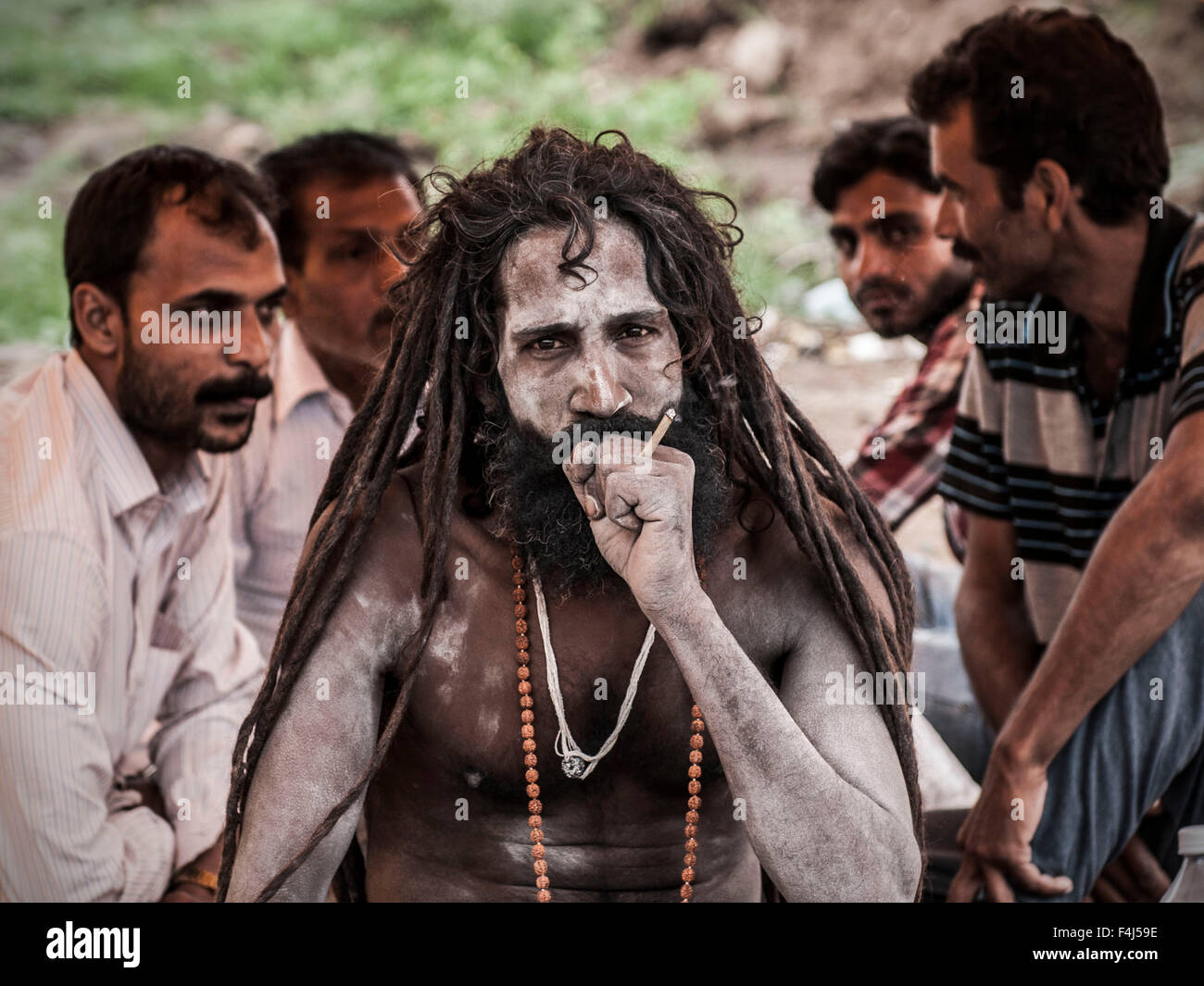 A Sadhu smoking at the Kumbh Mela - Stock Image