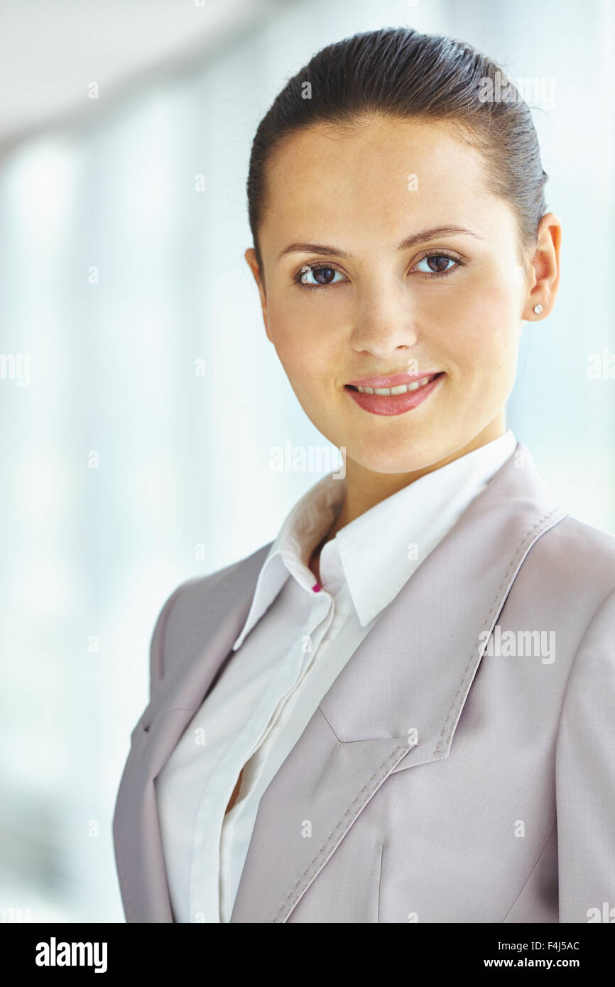 Pretty young businesswoman in formalwear looking at camera - Stock Image