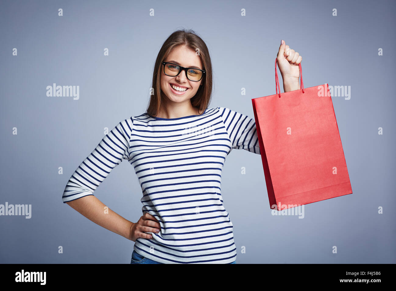 Happy young shopper with red paperbag looking at camera - Stock Image