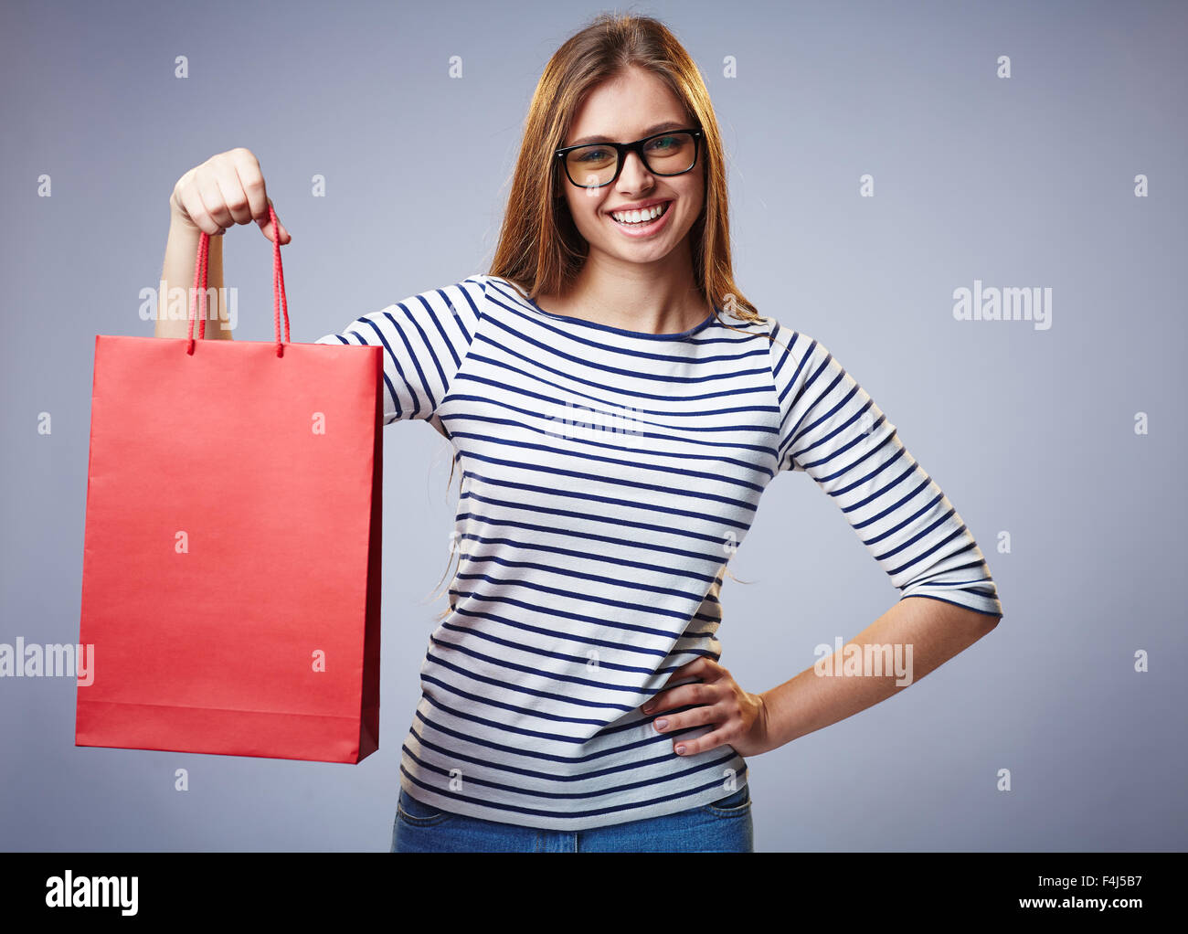 Pretty shopper showing red paperbag and looking at camera - Stock Image