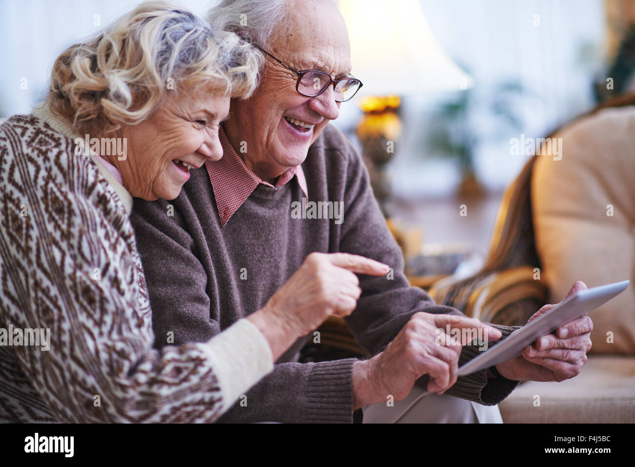 Happy seniors networking together at home - Stock Image