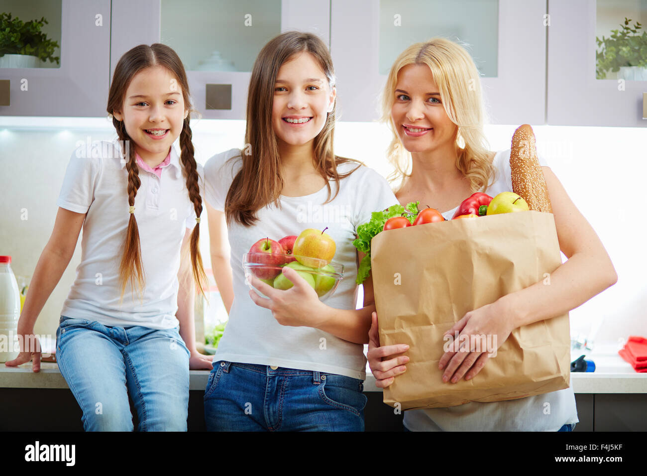 Young woman and two adolescent girls looking at camera in the kitchen - Stock Image