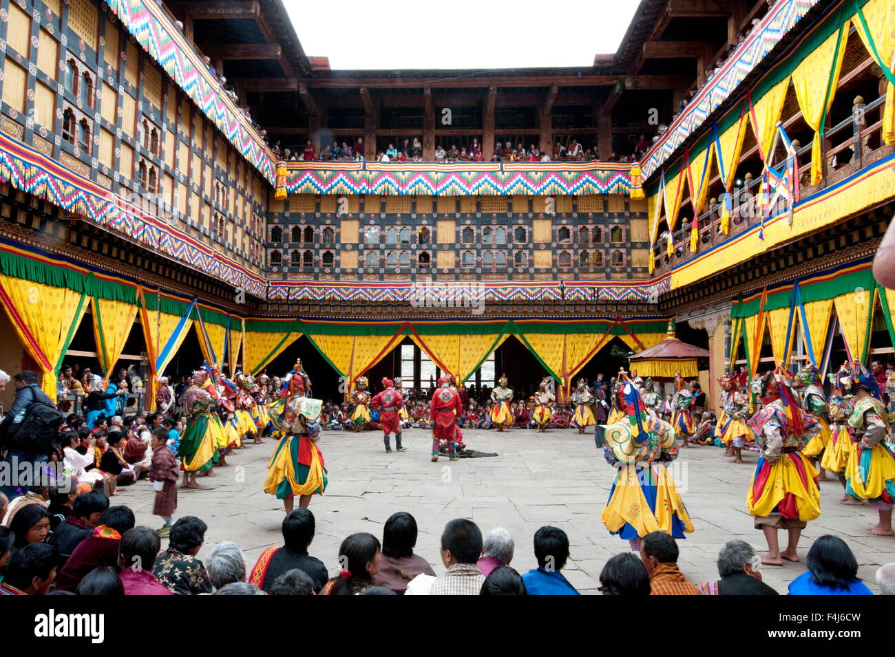 Monks performing religious ceremonial dances in the inner monastery courtyard at the Paro Tsechu, Paro, Bhutan - Stock Image