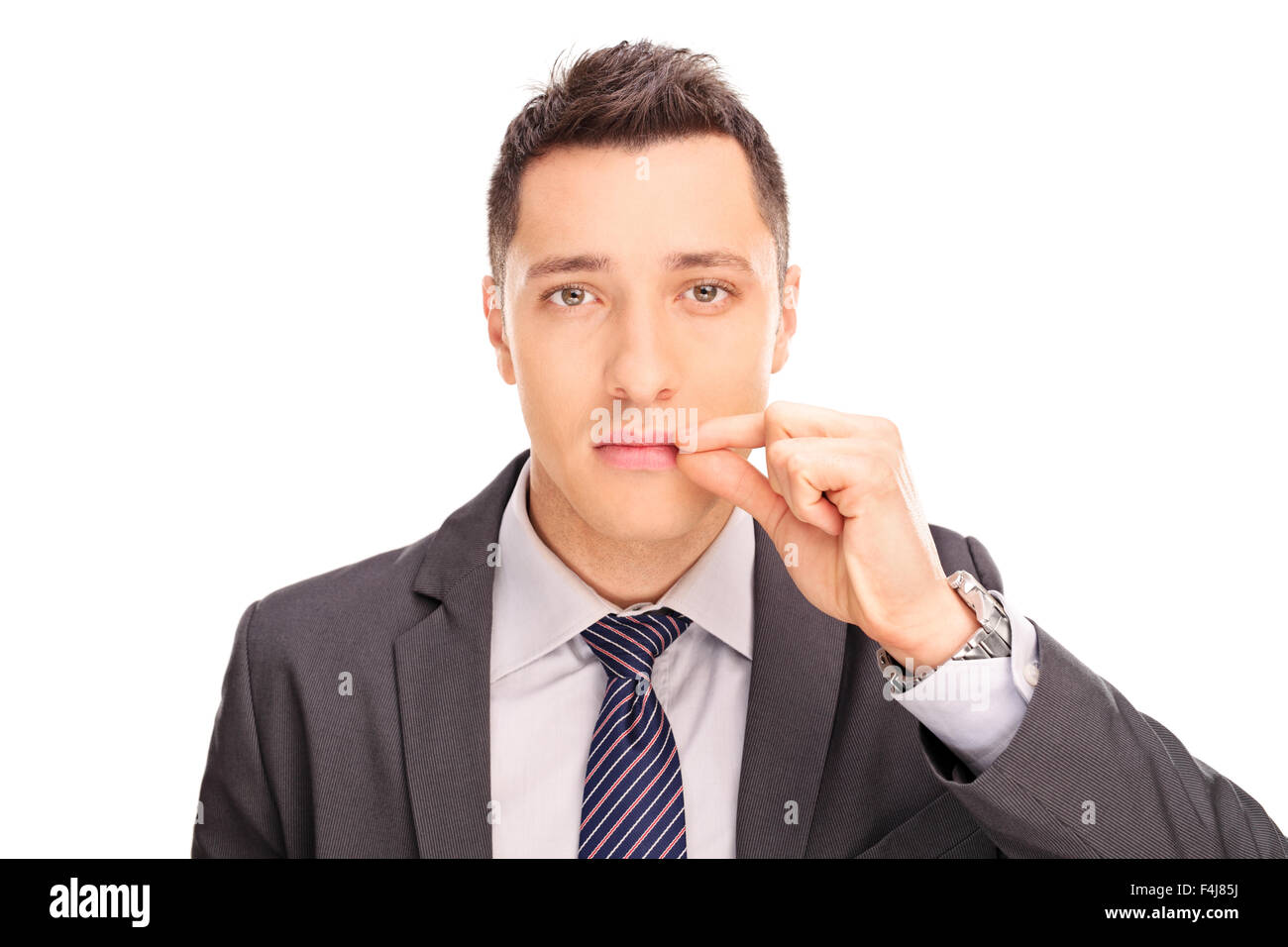 Close-up on a young businessman holding his hand on his lips symbolizing shut mouth isolated on white background - Stock Image