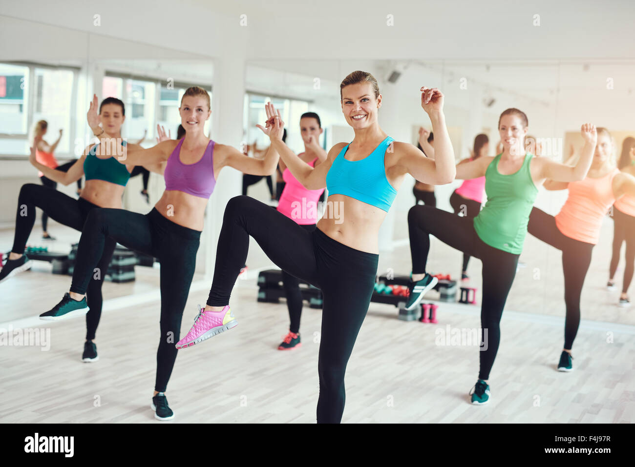 Large group of attractive toned fit young women enjoying an aerobics workout at the gym in a health and fitness - Stock Image