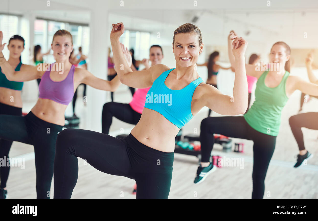 Group of enthusiastic young women in bright colored clothes practicing aerobics in a gym in a health and fitness - Stock Image