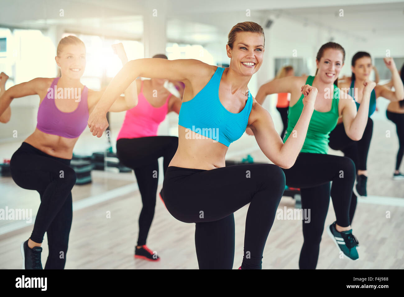 fitness, sport, training, aerobics and people concept - group of people working out in gym - Stock Image