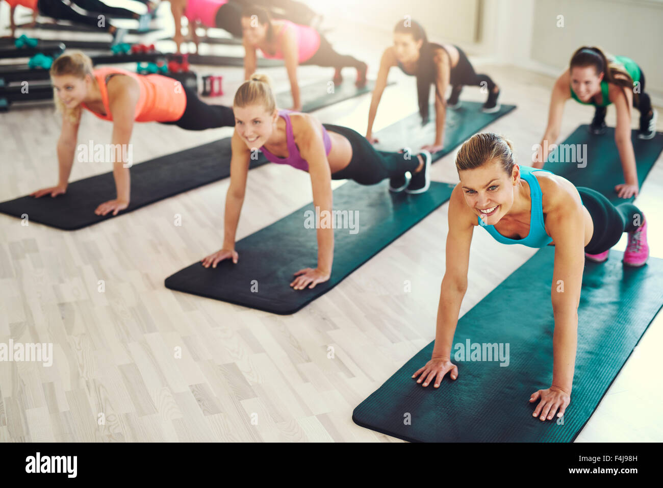 Large group of young women working out in a gym doing push ups in an aerobics class in a health and fitness concept - Stock Image