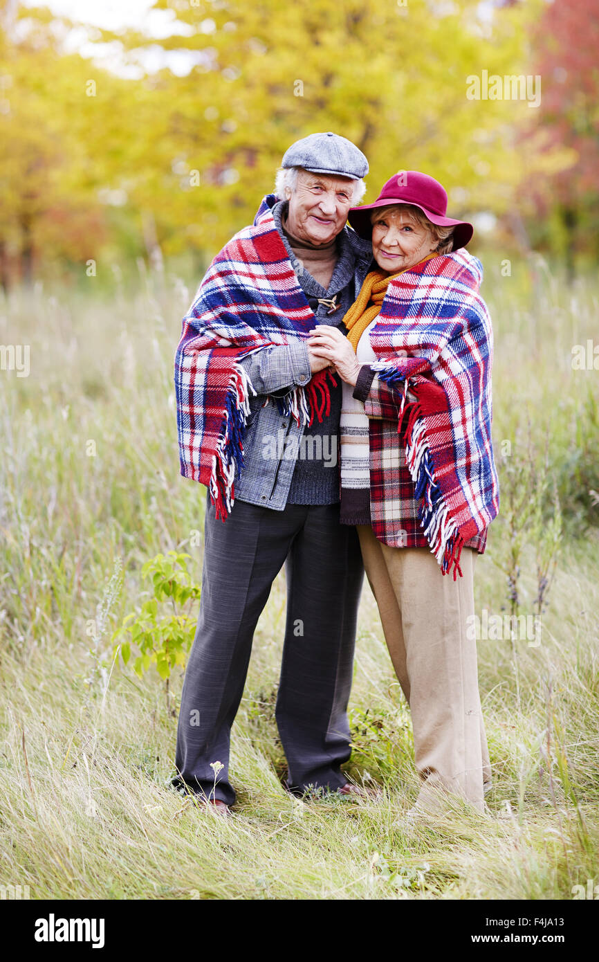 Old man and woman in warm clothes looking at camera in natural environment - Stock Image