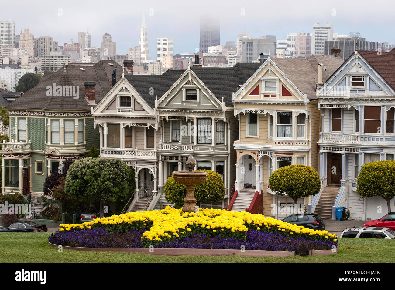 Wooden houses, Victorian houses, also Painted or Beautiful Ladies, Alamo Square, behind Downtown San Francisco skyscrapers - Stock Image