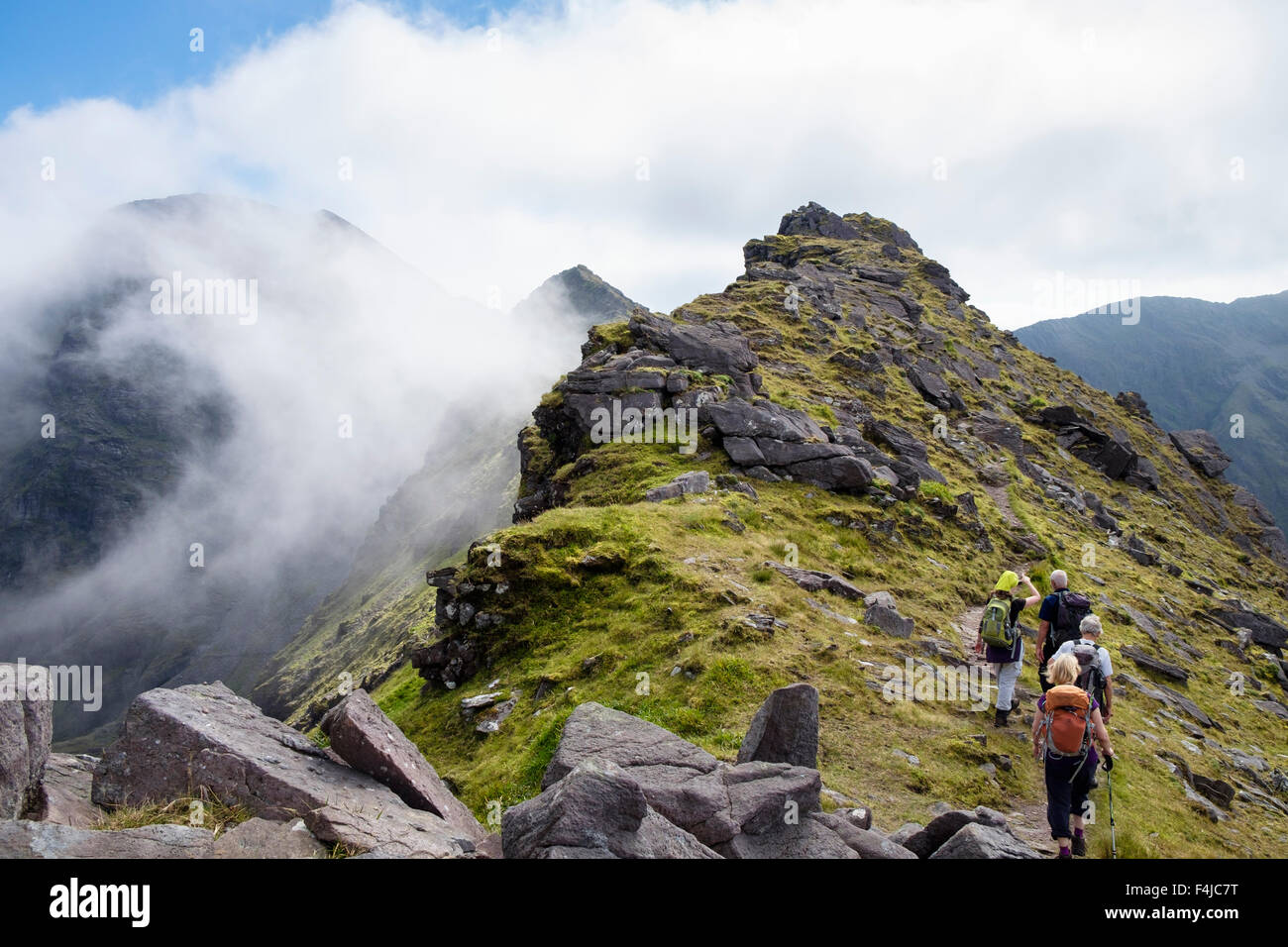 Low cloud on Carrauntoohil from Beenkeragh or Binn Chaorach ridge with hikers hiking in MacGillycuddy Reeks County - Stock Image