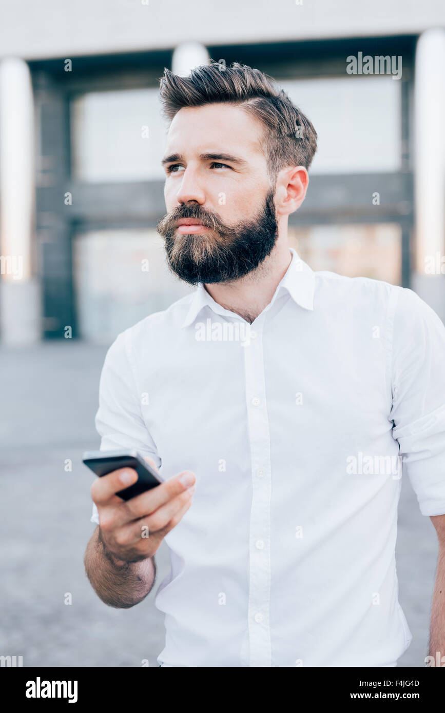 Half length of young handsome blonde caucasian modern businessman holding a smartphone, overlooking right, pensive - Stock Image