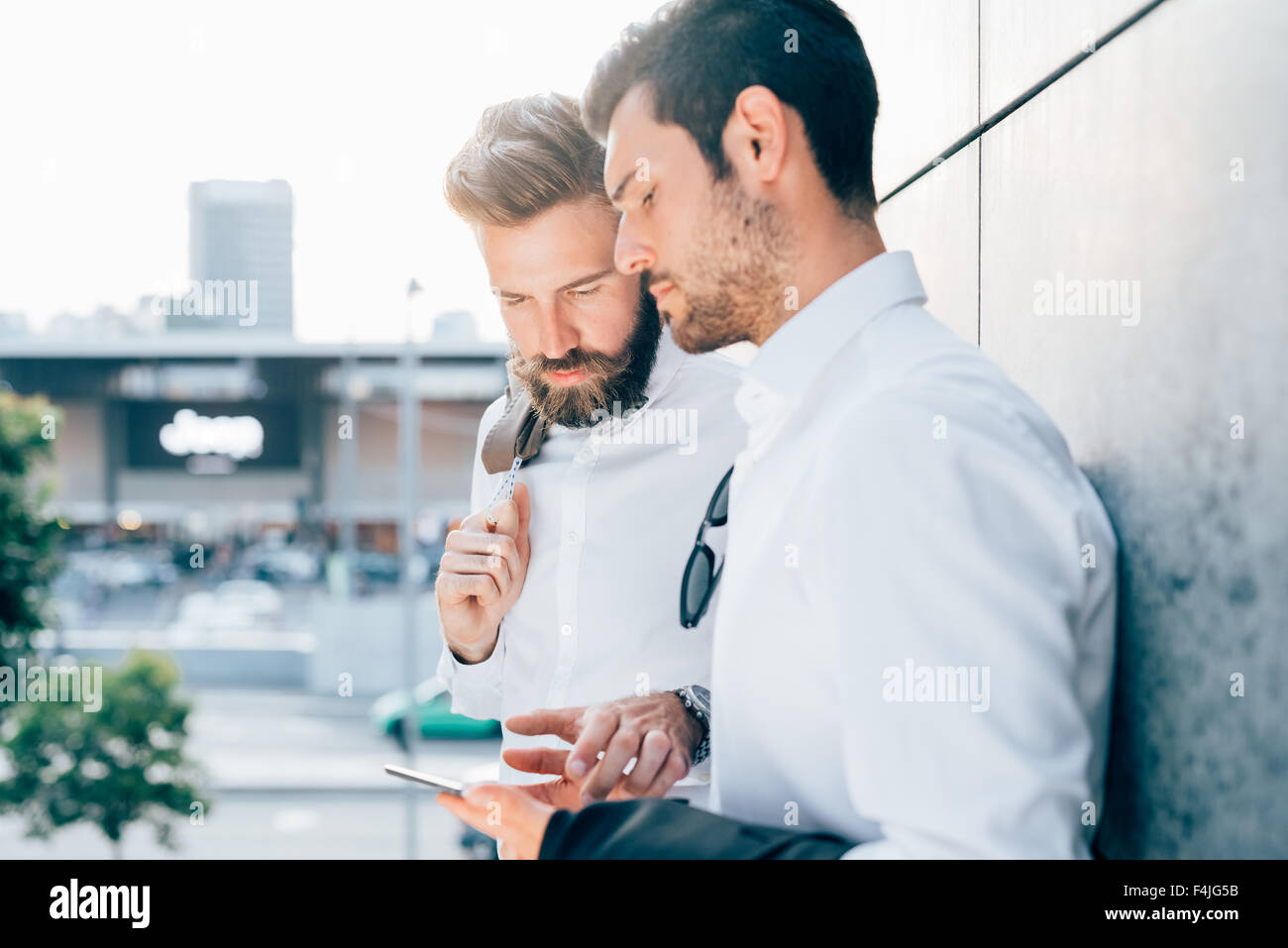 Half length of two young bearded blonde and black hair modern businessman, leaning against a wall, using tablet, - Stock Image